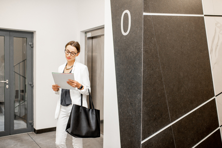 Young business woman in white suit standing in the walkhall near the elevator at the modern residential building