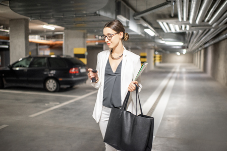 Young business woman walking with car keys in the underground parking of the new residential building