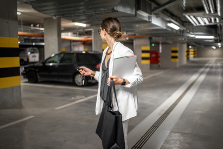 Young business woman walking with car keys in the underground parking of the new residential building Stok Fotoğraf - 113401377