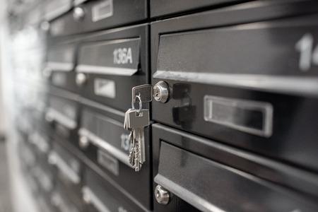 Buzones de correos de metal residencial tradicional con números de apartamento en el moderno edificio multifamiliar