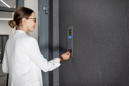 Young business woman in white suit touching the intercom with keychain opening the door of residential modern building Фото со стока