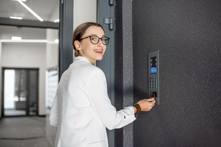 Young business woman in white suit touching the intercom with keychain opening the door of residential modern building Stockfoto