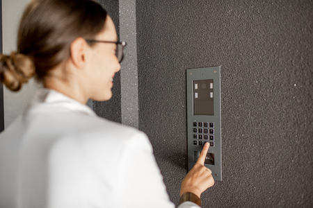 Young business woman in white suit entering code on the intercom keyboard of the residential modern building Stock Photo