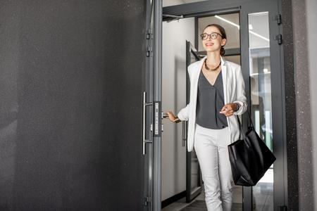 Mujer de negocios joven en traje blanco saliendo del edificio residencial apresurándose a trabajar Foto de archivo