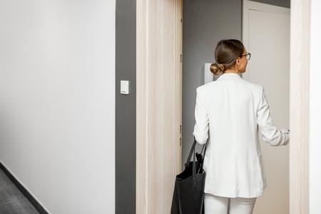 Mujer de negocios entrando en un nuevo apartamento desde el pasillo blanco del edificio residencial