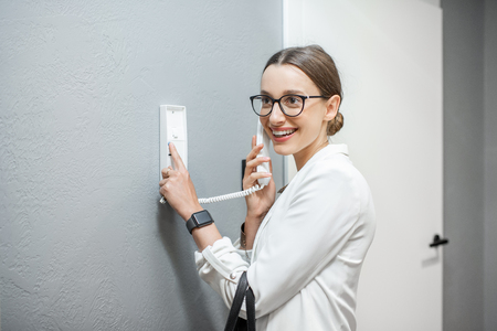 Woman opening the door from the intercom phone standing in the apartment