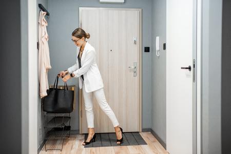 Jonge zakenvrouw in de hal van het appartement die terugkeert na de baan Stockfoto