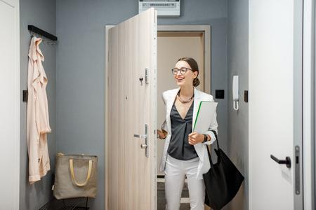 Jeune femme d'affaires entrant dans l'appartement revenant du travail à la maison Banque d'images