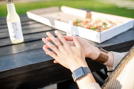 Mujer rociando antiséptico en las manos antes de comer pizza al aire libre