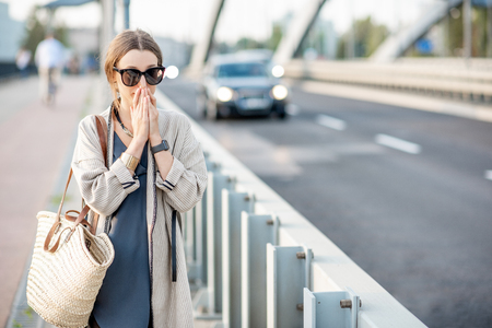 Woman closing her nose feeling bad because of the air pollution on the bridge with traffic in the city