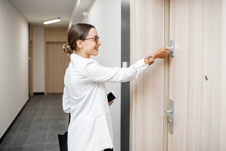 Young businesswoman opening apartment door with key standing in the corridor of the modern residential building