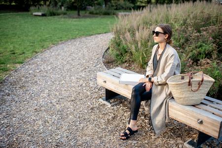 Jeune femme élégante s'asseyant sur le banc au parc public moderne Banque d'images
