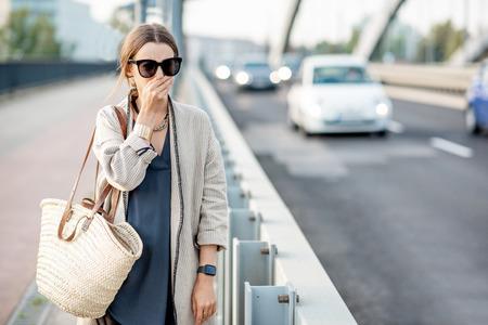 Frau, die ihre Nase schließt und sich wegen der Luftverschmutzung auf der Brücke mit dem Verkehr in der Stadt schlecht fühlt