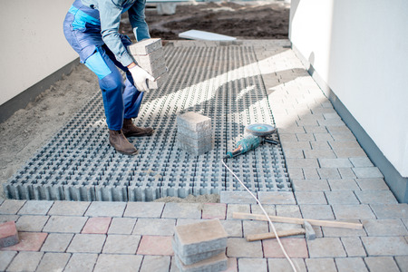 Builder carrying paving tiles on the construction site, cropped image with no face Stockfoto