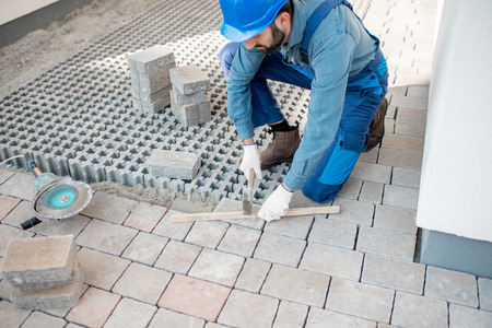Builder laying paving tiles on the construction site, cropped image with no face