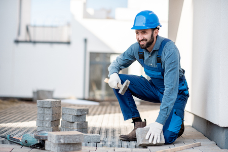 Builder in uniform laying paving tiles on the construction site with white houses on the background