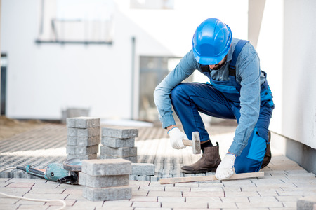 Builder in uniform laying paving tiles on the construction site with white houses on the background Imagens - 112132558