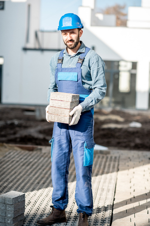 Porait of a builder in uniform holding paving tiles on the construction site with white houses on the background