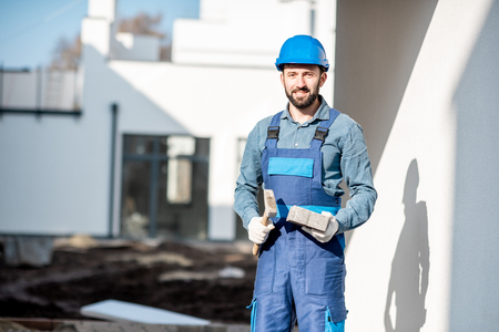 Porait of a builder in uniform holding hummer and paving tile on the construction site with white houses on the background