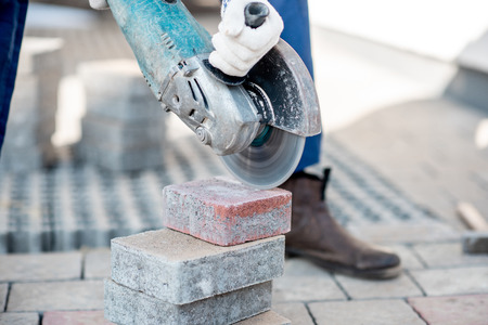 Builder in uniform cutting paving tiles with electric cutter, close-up view