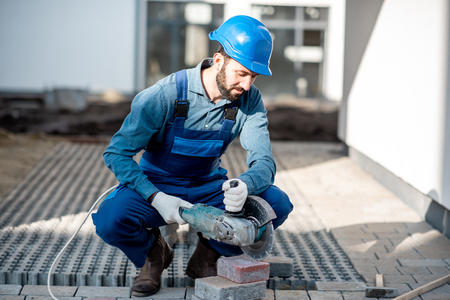 Builder in uniform cutting paving tiles with electric cutter on the construction site with white houses on the background