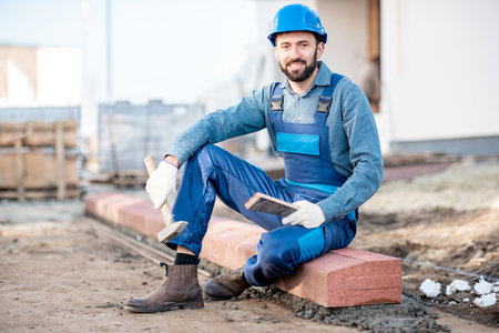 Portrait of a handsome builder in uniform mounting road borders on the construction site