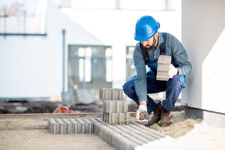 Bouwer in uniform leggen van bestrating tegels op de bouwplaats met witte huizen op de achtergrond Stockfoto