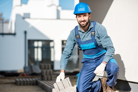 Portrait of a builder in uniform laying paving tiles on the construction site with white houses on the background 版權商用圖片