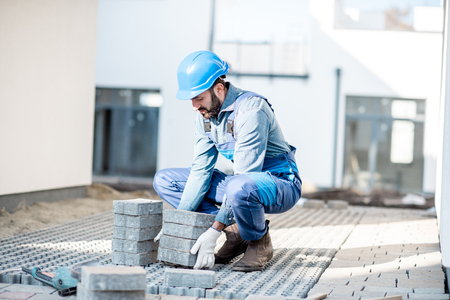 Builder in uniform laying paving tiles on the construction site with white houses on the background Imagens - 112132640