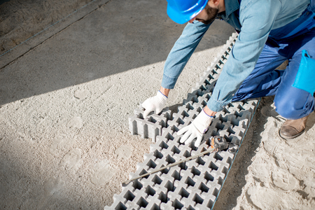 Builder laying paving tiles with holes for grass on the construction site, view from above Stockfoto