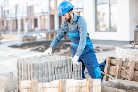 Builder in uniform taking paving blocks from the pallet working on the construction site outdoors Stockfoto - 112132679