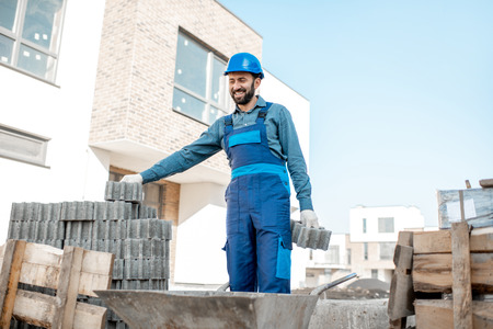 Builder in uniform taking paving blocks from the pallet working on the construction site outdoors Stockfoto
