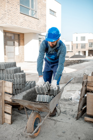 Builder loading paving tiles into the pushcart standing on the construction site Stockfoto