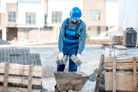 Builder loading paving tiles into the pushcart standing on the construction site Stock Photo