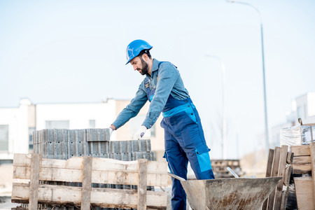 Builder in uniform taking paving blocks from the pallet working on the construction site outdoors Stock Photo