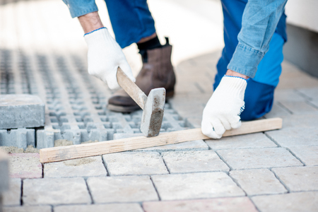 Builder laying paving tiles on the construction site, close-up view with no face