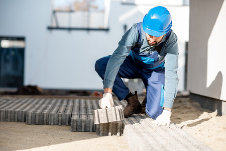 Builder in uniform mounting paving tiles on the construction site with white houses on the background