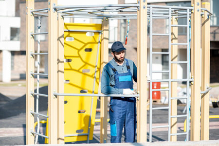 Handsome workman in uniform mounting ladder for kids playing on the playground outdoors
