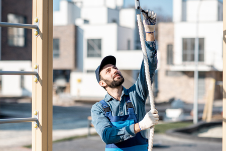 Handsome workman in uniform mounting rope for climbing on the playground outdoors