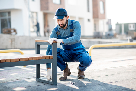 Handsome workman in uniform mounting a new bench on the playground outdoors