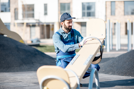 Handsome workman in uniform mounting kids swing on the playground outdoors