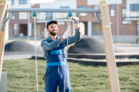 Handsome workman in uniform mounting swing on the playground outdoors Stockfoto