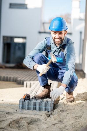 Builder in uniform mounting paving tiles hammering a pile on the construction site outdoors