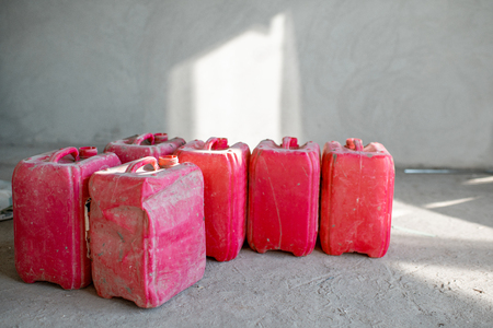 Red used canisters on the construction site indoors on the grey wall background