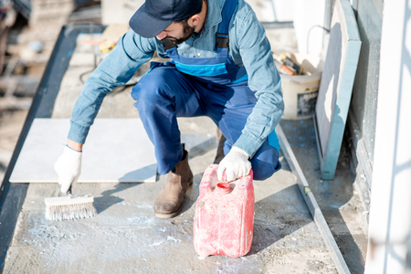 Workman in uniform priming concrete with brush for tiles lying on the balcony Stockfoto