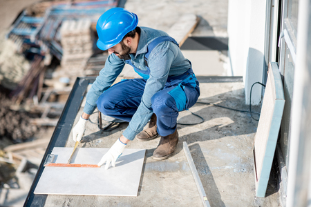 Workman in uniform mounting ceramic tiles on the balcony at the construction site