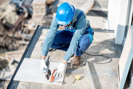 Ouvrier en uniforme de montage de carreaux de céramique sur le balcon du chantier de construction