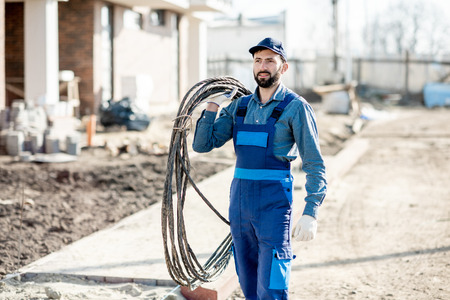 Portrait of a handsome electrician in uniform with power cable for the network on the construction site