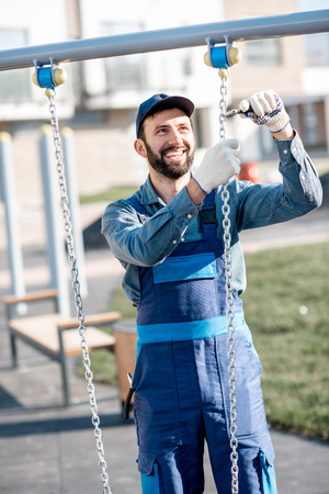 Handsome workman in uniform mounting swing on the playground outdoors Stock Photo