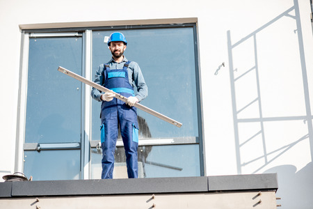 Portraiit of a builder in uniform standing with level on the balcony of a new house on the construction site Banco de Imagens